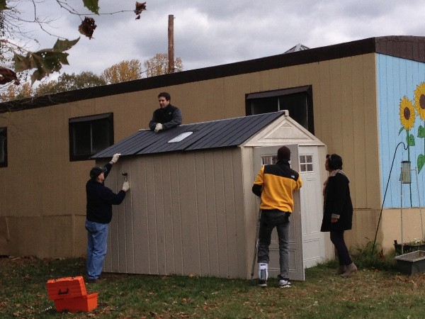 Young AFCEANs place the roof on an outdoor supply shed, which the chapter donated to Fort Belvoir Elementary School in November.